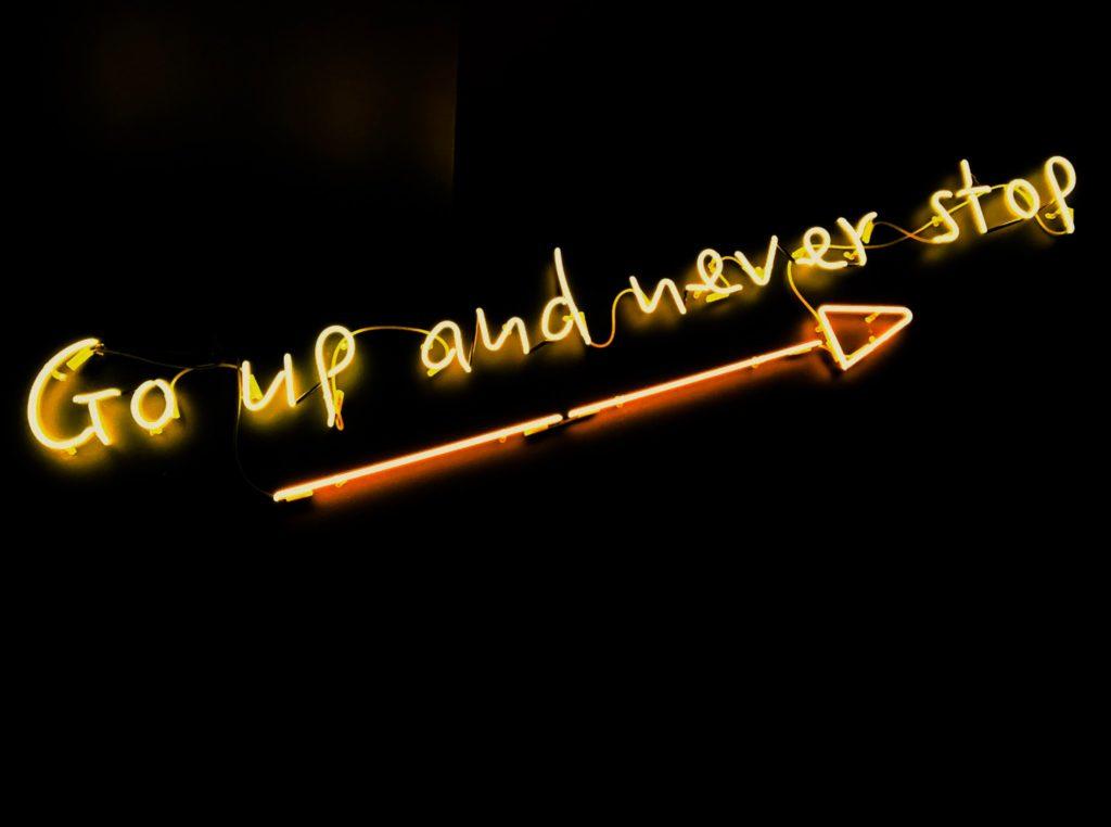 Go up and never stopという英単語のデザインのネオンサインの画像